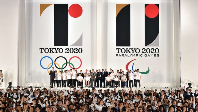 People wave Olympic flags as the logo marks of the Tokyo 2020 Olympic and Paralympic Games are unveiled at the Tokyo city hall on July 24, 2015.