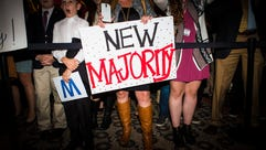 "A woman holds a ""New Majority"" sign during the Republican"