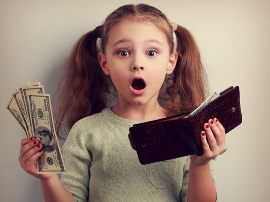 Cute surprising kid girl holding wallet and dollars