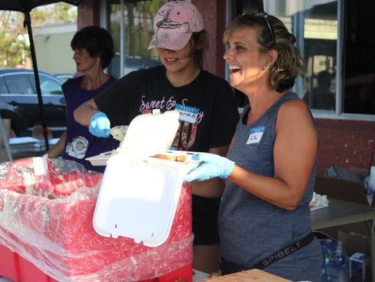 Liz Tirrell (right) and a volunteer prepare a meal.