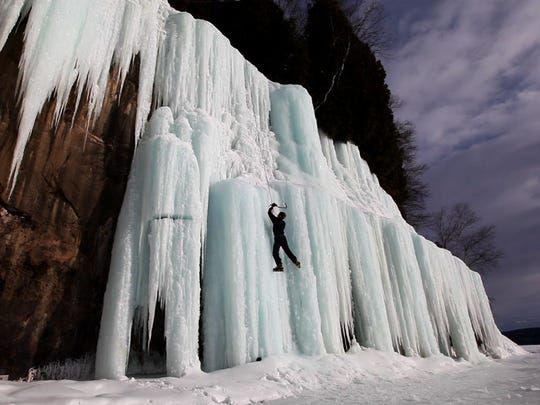 An ice climber ascends frozen water falls on Grand Island near Munising, MI. In the winter, Grand Island is only accessible when Munising Bay freezes over. Pictured Rocks National Lakeshore has more climbing that can be reached by land. The area has hundreds of climbs that are created when water flowing over sandstone cliffs freezes.