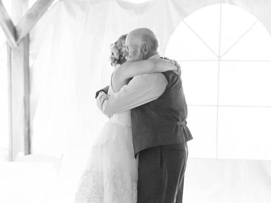 Erin Saddlemire VanNosdall hugs her father, Gary ''Bonz' Saddllemire, at her wedding.
