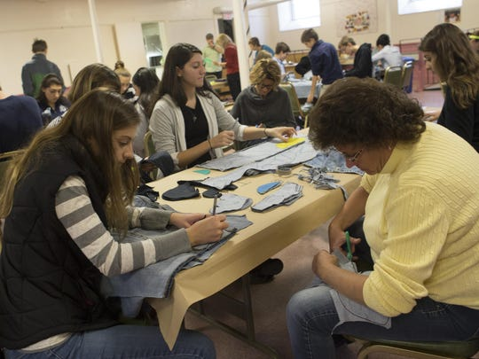 More than 40 volunteers convened in the basement of the United Methodist Church in Madison on Nov. 22, to cut pattern pieces out of donated blue jeans that will be made into shoes for children in Uganda.