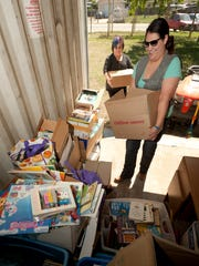 At top, Robert Isquierdo is organizing an effort to open a library in London. Above, Jessica Graves, right, and Karina Santoyo sort books donated to the effort to open a library. A deal for a proposed site could be reach this week.