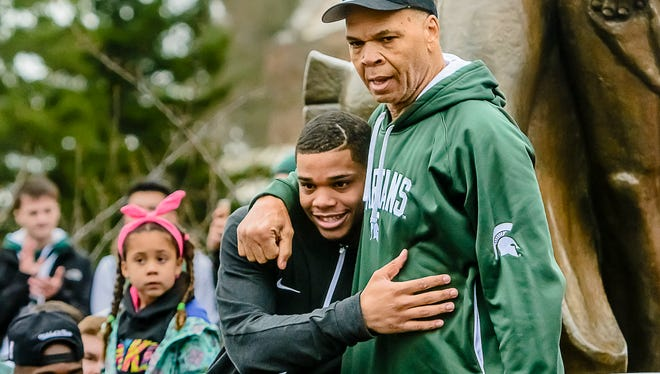 Raymond Bridges ,right, hugs his son MSU Freshman men's basketball player Miles Bridges after he announced his decision to remain in school next season.