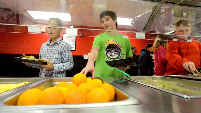"Anthony Giuliano, 13, left, makes his way through the lunch line as Sam Miller, 13, reaches for an orange in the Clyde A. Erwin Middle School cafeteria on April 8. ""They serve the same stuff a lot,"" Sam said of the school lunches."