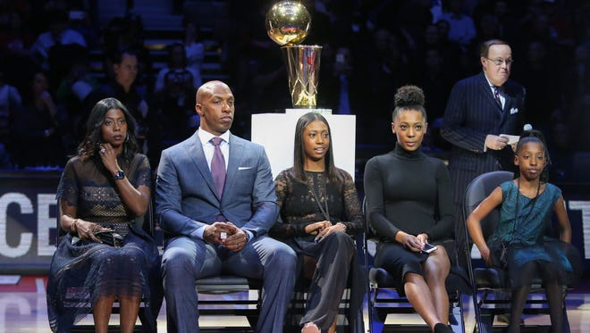 Chauncey Billups sits with his family before his jersey is retired at the Palace.