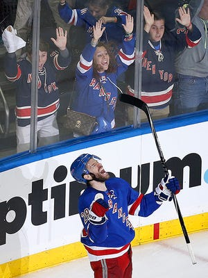 Rangers center Dominic Moore scores with 2:25 left in Saturday's game.