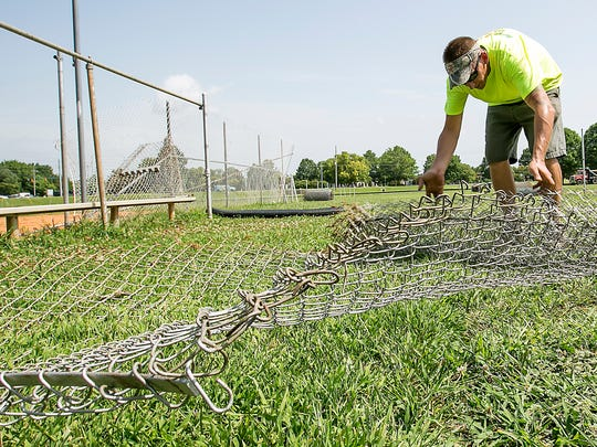 Workers begin to take down the fencing to the two practice fields at McKnight Park as site work begins for the Miracle Field.