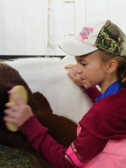 Madison Hazel, 10, brushes Promise O'Mine, a 24-year-old