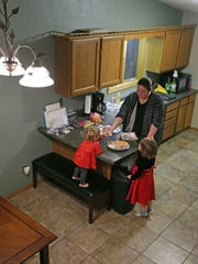 Megann Hooyman and her daughters, Rylee, left, and Zoey, check out  Christmas cookies Tuesday at the Appleton duplex the family is renting as their home is repaired following an early December fire.