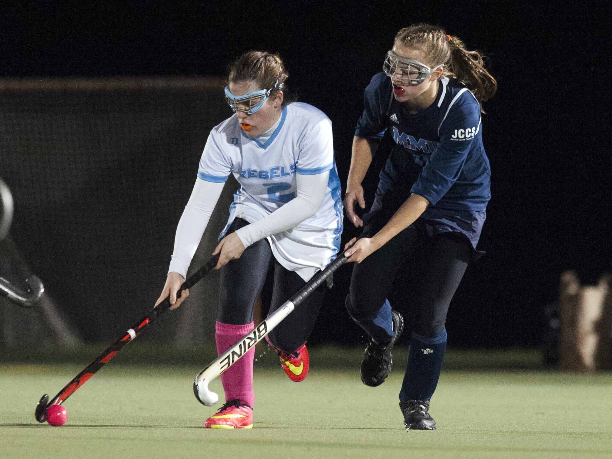 South Burlington's Kate Hall (2) runs past MMU's Ginny Churchill (11) during a Division I high school field hockey semifinal game at Middlebury College.