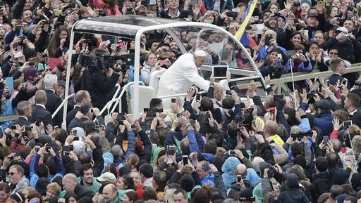 Pope Francis salutes faithful in St. Peter's square at the Vatican, Sunday, April 5, 2015.