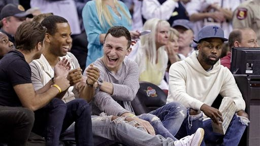 Cleveland Browns quarterback Johnny Manziel, third from left, laughs with friends at the end of a first round NBA playoff basketball game between the Boston Celtics and Cleveland Cavaliers Sunday, April 19, 2015, in Cleveland. The Cavaliers won the first game of the series 113-100. (AP Photo/Mark Duncan)
