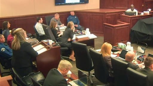 File - In this April 27, 2015 file photo, taken from a Colorado Judicial Department video, Colorado theater shooter James Holmes, far left rear in light-colored shirt, watches during testimony by witness Derick Spruel, upper right, on the second day of his trial in Centennial, Colo. Standing at left is prosecutor Lisa Teesch-Maguire. Defense attorneys have urged jurors not to let emotions sway them, but with weeks of harrowing testimony still to come, experts say James Holmes' lawyers will have a difficult time convincing jurors to put sympathy behind them as they decide whether he was legally insane when he killed 12 people and injured 70 others in July 2012. (Colorado Judicial Department via AP, Pool, File)