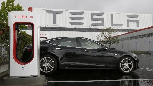A car is parked at a Tesla charging station outside of the Tesla factory in Fremont, Calif., on May 14, 2015.