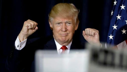 Republican presidential candidate Donald Trump pumps his fists as he takes the stage during a campaign rally Saturday, Nov. 5, 2016, in Tampa, Fla.