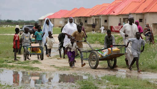 In this photo taken Saturday, Aug. 27, 2016, children displaced by Islamist extremists wheel food handed out to them at the Bakassi camp in Maiduguri, Nigeria. Local lawmakers in northeast Nigeria are investigating fresh allegations that officials have diverted food aid intended for Boko Haram refugees.
