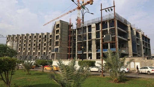 An unfinished hotel in Basra, 340 miles (550 kilometers) southeast of Baghdad, Iraq, Thursday, Dec. 1, 2016. War-weary Iraq hinges hopes on OPEC agreement to cut production to meet the massive needs of its costly, two-year-old war against the Islamic State extremist group, and to refresh its ailing, oil-reliant economy hammered by plummeted oil prices. (AP Photo/Nabil al-Jurani)