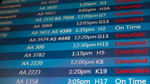 A screen displays flight status information at O'Hare International Airport on Sunday, Dec. 11, 2016, in Chicago. The wintry weather has forced airlines to cancel more than 1,000 flights at Midway and O'Hare airports as of late Sunday morning. (AP Photo/Nam Y. Huh)