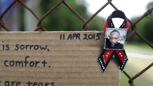 A ribbon with the image of Walter Scott is affixed to the fence with a message at the scene where Scott was fatally shot by a white police officer after he fled a traffic stop, Sunday, April 12, 2015, in North Charleston, S.C. The officer, Michael Thomas Slager, has been fired and charged with murder.