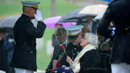 In this U.S. Army photo by Rachel Larue/Arlington National Cemetery, Marine Corps Commandant Gen. Robert B. Neller, left, salutes Annie Glenn, widow of John Glenn, following the American flag presentation during the graveside service for Glenn at Arlington National Cemetery in Arlington, Va., Thursday, April 6, 2017. Glenn, who died Dec. 8 at age 95, was laid to rest in a private burial attended by relatives and invited guests. His family scheduled the service for what would have been John and Annie Glenn's 74th wedding anniversary. (U.S. Army photo by Rachel Larue/Arlington National Cemetery via AP)