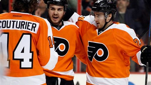 Philadelphia Flyers' Sean Couturier, Zac Rinaldo and Matt Read, from left, celebrate Rinaldo's goal during the second period of an NHL hockey game against the Buffalo Sabres, Sunday, April 6, 2014, in Philadelphia. Rinaldo was ejected in the third period, incurring a match penalty for a hit to the head of Chad Ruhwedel. The Flyers won 5-2.  (AP Photo/Tom Mihalek)