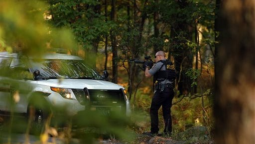 A Pennsylvania state trooper draws his weapon in a wooded area on Snow Hill Road in Price Township, Pa., during a huge manhunt for suspected killer Eric Frein on Sunday, Sept. 21, 2014, near Canadensis, Pa. Authorities have had no confirmed sightings of Frein but said they found an assault rifle that he was carrying in the dense northeastern Pennsylvania woods. (AP Photo/The Scranton Times-Tribune, Butch Comegys)
