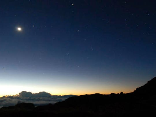 The moon hangs above the horizon as the glow of the sun begins to fill the sky in front of the summit of Haleakala volcano in Haleakala National Park on Hawaii's island of Maui, Tuesday, Jan. 24, 2017. Park officials say the sunrise on Haleakala attracts over a thousand people a day, resulting in an overload of visitors and creating a safety hazard. As a result, anyone wanting to see the sunrise on the summit will now be required to make reservations in advance and pay a small fee.