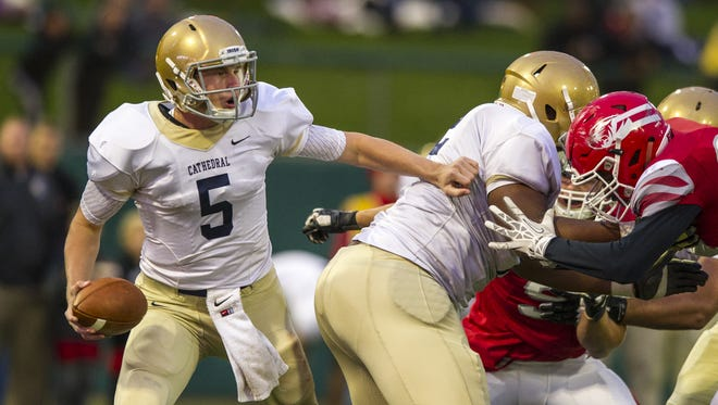 Cathedral High School senior quarterback Max Bortenschlager (5) is pressured in the backfield with the ball during the first half of action of an inaugural IHSAA varsity football game being played at Victory Field in Indianapolis, Friday, October 2, 2015.