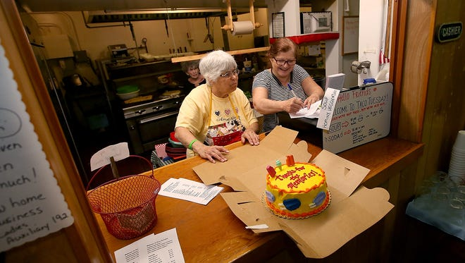 "Kathleen Painter, Madame President of the Auxiliary, left, and daughter Loreen Anderson, Auxiliary Secretary, look over food orders as a cake adorned with ""Thanks For The Memories"" sits on the counter during the last Taco Tuesday at the Bremerton Eagles on Tuesday."
