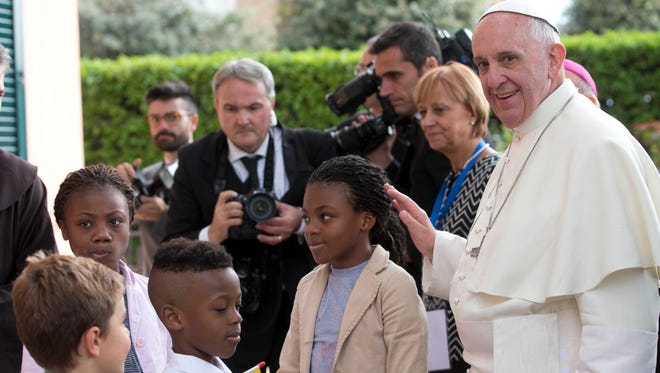 Pope Francis is welcomed by children as he arrives  to the Caritas Reception Center at St. Mary of the Angels, near Assisi, Italy, on Oct. 4, 2013.