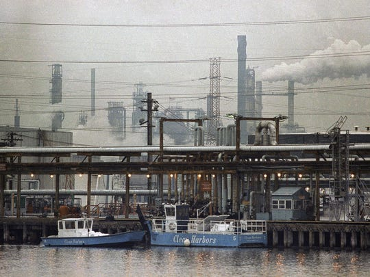 In this Jan. 9, 1990 file photo, two clean harbor cleanup boats work in the Arthur Kill waterway in front of the Exxon oil refinery in Linden, N.J. Days earlier, some 546,000 gallons of No. 2 heating oil spilled from an Exxon underwater pipeline, temporarily closing the waterway between New Jersey and Staten Island, N.Y.