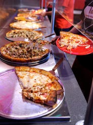 Diners grab slices of pizza on their plates during