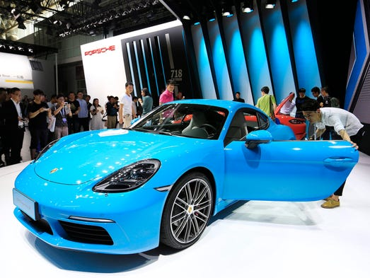 Visitors look at the new 2017 Porsche 718 Cayman vehicle