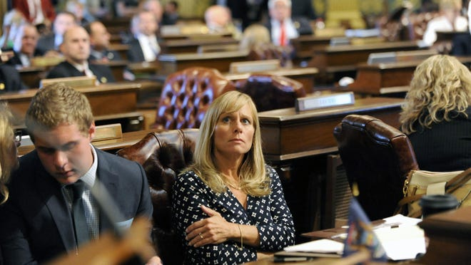 State Rep. Cindy Gamrat watches the vote board light up Thursday in the state House of Representatives in Lansing. She was expelled from the House early Friday morning.