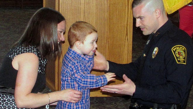 Newly promoted Elmira police Lt. Kristen Thorne is congratulated by his wife Breanna and his son Logan on Tuesday following a swearing-in ceremony.