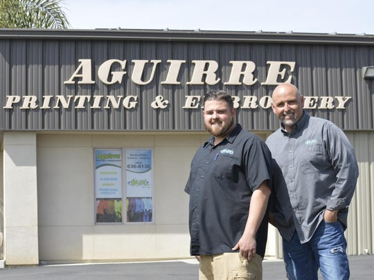 Rigo Aguirre, left, and his son Ryan Aguirre stand by Aguirre Printing and Embroidery, 9610 W. Nicholas St. on Wednesday.