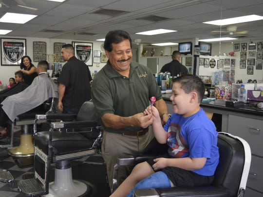 Carlos Medina, owner of Carlos Sportsmen Barber shop, hands 6-year-old Dominic Felix a loli pop after getting a back to school hair cut.