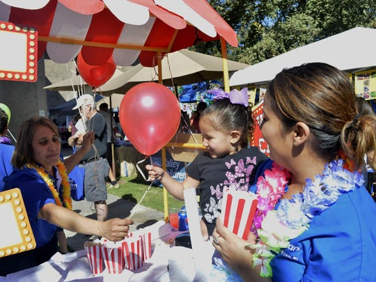 Malaya Mendaes, 3, grabs a balloon from the raffle ticket booth, Saturday, at the Visalia Medical Clinic's 75th Anniversary Health Festival.