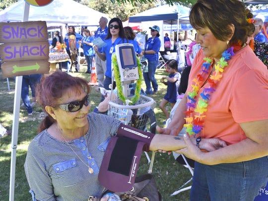Rosa Bines, Certified Medical Assistant at Visalia Medical Clinic, checks Terrie Hernandez's of Visalia, blood pressure, Saturday at the Visalia Medical Clinic's 75th Anniversary Health Festival.