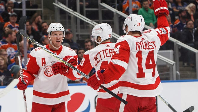 Red Wings forward Justin Abdelkader, left, celebrates a goal with teammates Henrik Zetterberg, center, and Gustav Nyquist during the first period of Sunday's win in Edmonton Oilers.