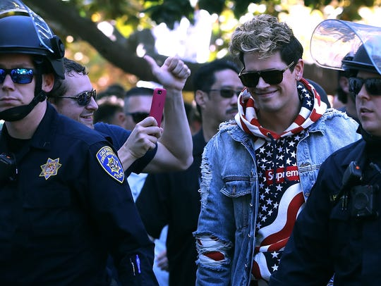 Right-wing commentator Milo Yiannopoulos is escorted