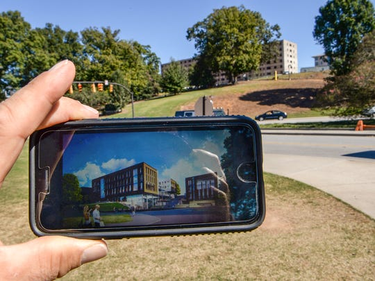 Clemson University's future College of Business, whose artist's rendering is visible here on a cell phone, will be located just below the old Clemson House, in the background. Clemson House still stands atop a hill along State 93 but will be torn down. The $87 million project is one of the most important academic structures to be constructed on campus in a century, said the business college dean, Bobby McCormick.