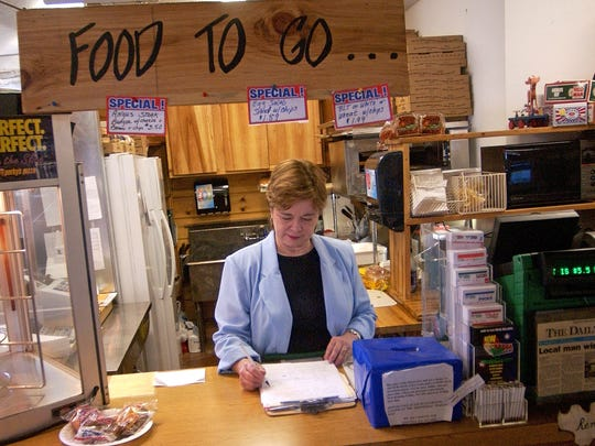 Carol Burks, co-owner of the Greenville Trading Post, does paperwork while working behind the counter in Greenville on Friday, Oct. 14, 2005.