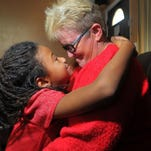 Robin Whiting gives her daughter Jenna Whiting a hug as her other daughters look on. All three children are adopted.