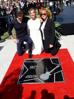 Tim McGraw and Faith Hill with Reba McEntire, who presented the couple at the ceremony, pose with Hill's star on the Walk of Fame on Wednesday, Oct. 5, 2016 in downtown Nashville.