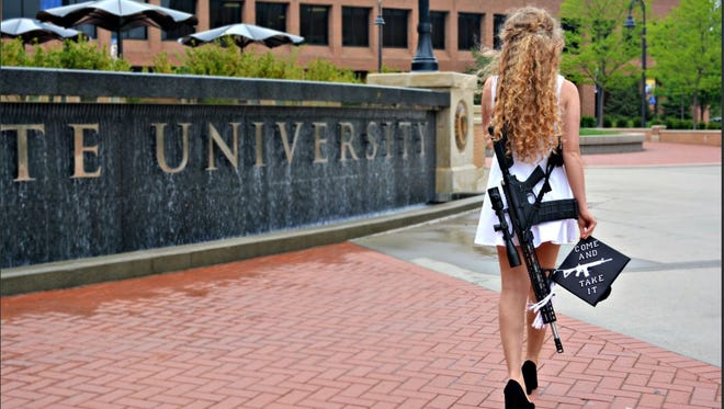 Kaitlin Bennett poses with an AR-10 rifle and graduation cap after the 2018 commencement ceremony at Kent State University on May 12, 2018.