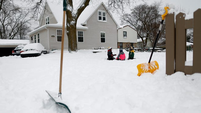 Siblings Ernesto and Gabriela Tabares along with their cousin Diego Tabares work on making a turtle sculpture out of the snow in Green Bay, Wis. on Tuesday, Dec. 29, 2015.