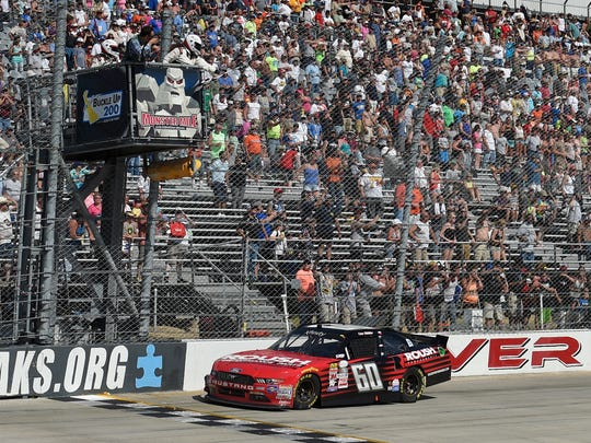 Chris Buescher takes the checkered flag to win the NASCAR Xfinity Series race on Saturday at Dover International Speedway.